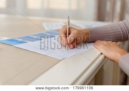 Focus on close up female hand writing file in hospital