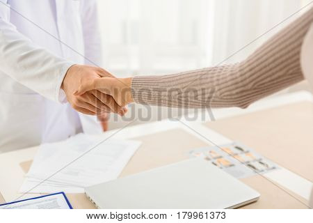 Close up shaking hands between therapeutic and female. She thanking doctor for treatment
