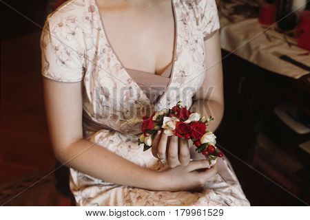 Beautiful sexy bride in stylish robe holding head wreath with white and red roses flowers in her hands morning wedding preparation in hotel room closeup