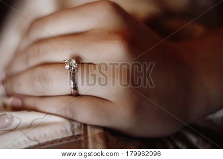 Closeup of silver engagement ring on hand beautiful bride in silver ring with diamond on finger morning before the wedding macro