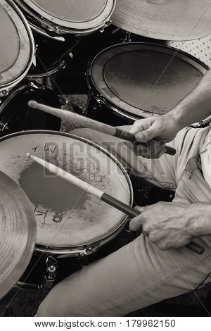 Drum kit. View from above. Drumsticks in hands. Monochrome.
