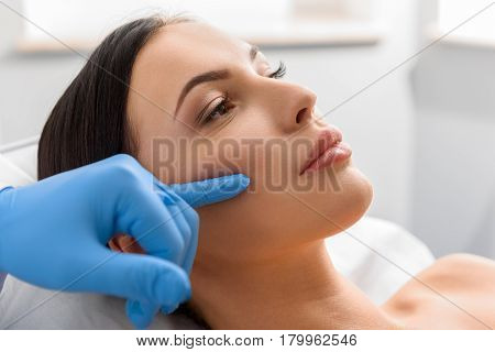 Side view of unconcerned female with fair skin in surgical room. Doctor telling about injection