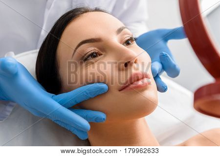 Calm woman receiving massage of face in beauty salon. She looking at mirror