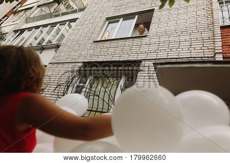 bride looking from window at bridesmaid with bunch of white decorative baloons balloons wedding decor closeup