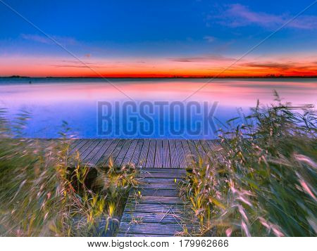 Long Exposure Image Of Blue And Orange Sunset Over Jetty On The Shore Of A Lake