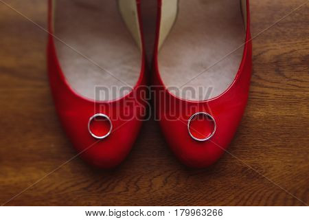 Two silver wedding rings on stylish red bride's shoes rustic wooden background couple of wedding rings on woman's shoes