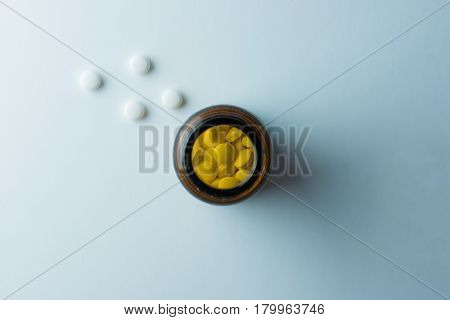 Medicine bottle or jar of pills, shot from above, with 4 tablets outside of bottle. On natural white background.