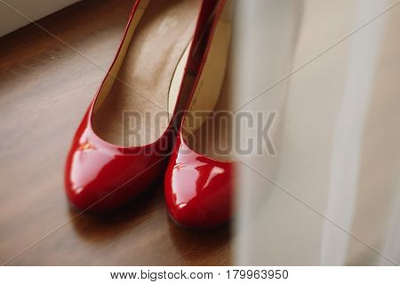Stylish red women's shoes on wooden floor elegant bride's shoes closeup on rustic background morning wedding preparation