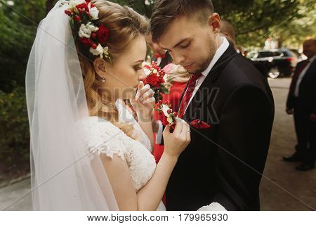 Beautiful bride putting on boutonniere on groom blonde bride in white wedding dress and veil pinning flowers on groom's black suit closeup