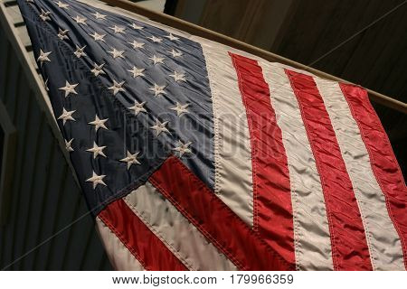 A red, white, and blue American Flag hanging on a pole blowing in  the wind