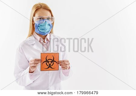 We are in danger. Concentrated female scientist is holding toxic contamination sign. Portrait. Isolated and copy space