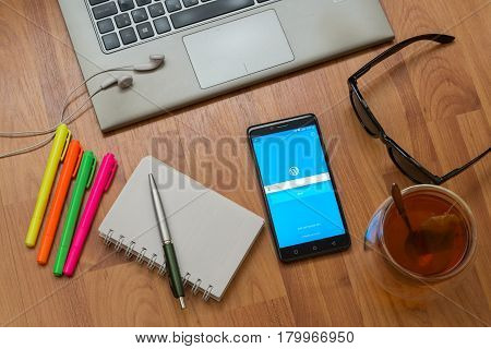 Nitra, Slovakia, april 3, 2017: Wordpress application in a mobile phone screen. Workplace with a laptop, an earphones, notepad, pen, tea, sunglasses and color markers on wooden background