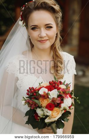 gorgeous bride smiling and holding wedding bouquet of red roses orchids. stylish wedding couple posing outdoors. tender sensual moment. floral arrangements. beautiful face