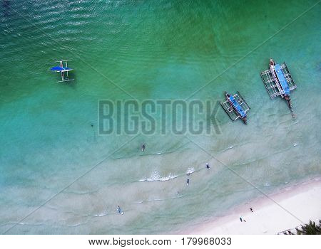 Aerial view of people landing on banca boats in the sea. Top view small beach with vacationing people banca boats and paddleboard on a sunny day. View from above.