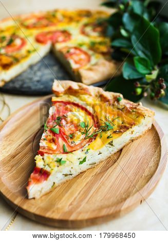 Slice of homemade tomato pie, pizza or quiche with curd cheese, eggs and fresh chopped parsley on a wooden plate perfect for summer picnic or snack, selective focus