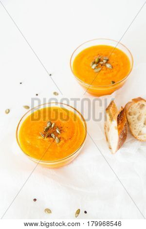 Two plates of pumpkin soup with seeds on a white background with space for your text