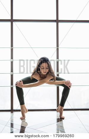 Yoga Woman Practice Near Window Yoga Room Studio Background. Yoga Concept.