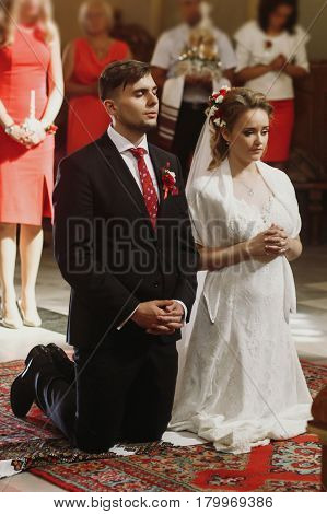 Bride and groom praying at wedding ceremony in church handsome groom and spiritual beautiful bride prayer on their knees during christian wedding ceremony