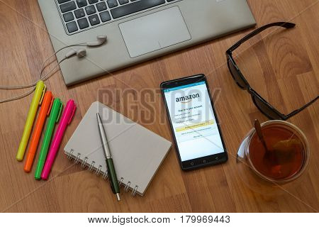 Nitra, Slovakia, april 3, 2017: Amazon application in a mobile phone screen. Workplace with a laptop, an earphones, notepad, pen, tea, sunglasses and color markers on wooden background