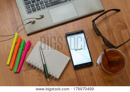 Nitra, Slovakia, april 3, 2017: Expedia application in a mobile phone screen. Workplace with a laptop, an earphones, notepad, pen, tea, sunglasses and color markers on wooden background