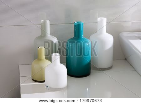 Bathroom with multi colored bottles and washbasin