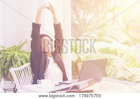 Business woman arms raised in office desk Relax and freedom concept after work hard