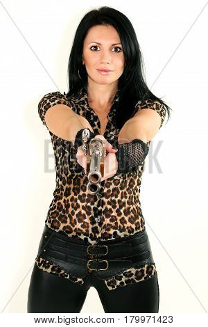 Portrait of a beautiful fashionable model girl in studio with a gun