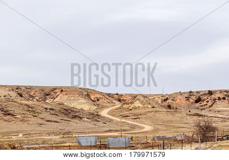 A fenced pasture with watering tubs and a red dirt winding road through hills and valleys in a Montana landscape