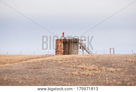 One newer and one old rusted oil tank with an attached ladder abandoned in a fenced pasture in spring Montana landscape