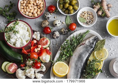 Mediterranean style food background. Fish vegetables herbs chickpeas olives cheese on grey background top view. Healthy food concept. Flat lay