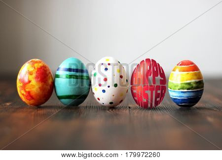 Easter colorful eggs on wooden background with egg shaped words Happy Easter