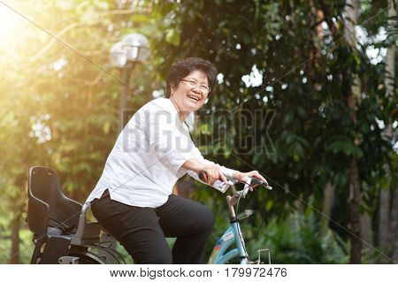 Active elderly Asian woman cycling, senior adult activity, riding bike outdoor in morning.