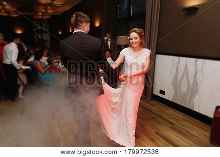 Happy newlywed couple dancing at evening wedding reception bride and groom ballroom dancing near smoke guests sitting and dining in the background