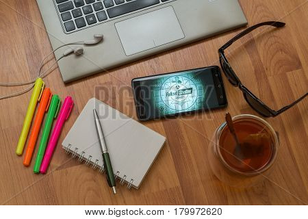 Nitra, Slovakia, april 3, 2017: Fallout Shelter application in a mobile phone screen. Workplace with a laptop, an earphones, notepad, pen, tea, sunglasses and color markers on wooden background