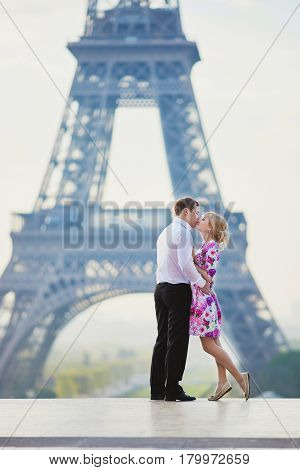 Couple Kissing In Front Of The Eiffel Tower In Paris, France