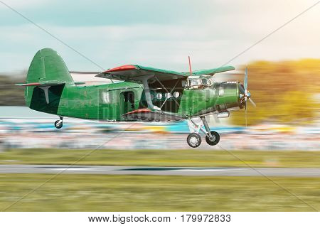 Retro green turbo propeller vintage aircraft flying over the car in the airport.