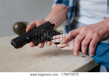 Fire weapon. Close up of a handgun un being in hands of a nice cute curious girl while learning how to shoot