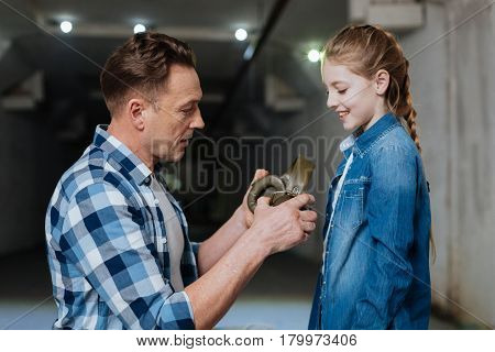 Wear them. Pleasant nice positive man looking at his daughter holding headphones and looking at his daughter while intending to wear them on her