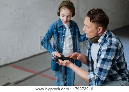 Not a toy. Pretty curious young girl looking at the handgun and taking it while wearing headphones
