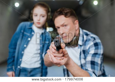 At gunpoint. Selective focus of a handgun being in hands of a nice pleasant handsome man while being pointed at you