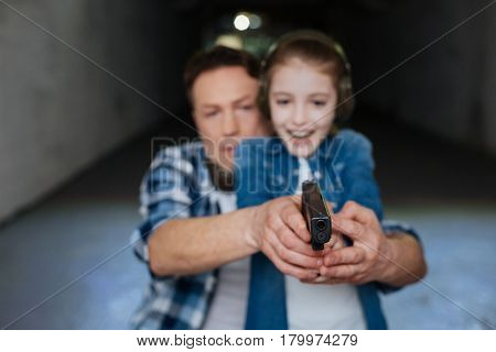 Self defense training. Cheerful positive pretty girl holding a handgun and directing it at the aim while having a shooting lesson