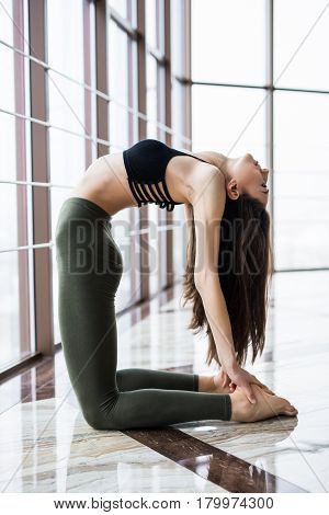 Ustrasana. Beautiful Yoga Woman Practice Near Window Yoga Room Studio Background. Yoga Concept.