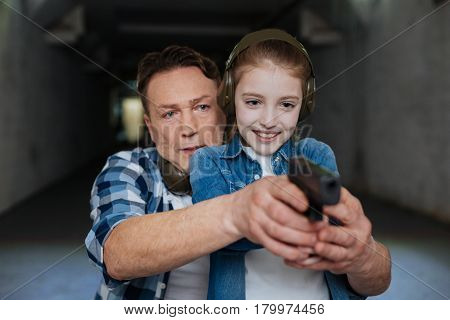 Do you see the aim. Nice handsome serious man standing behind his daughter and directing her handgun while teaching how to shoot