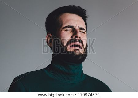Young man with a problem crying on gray background