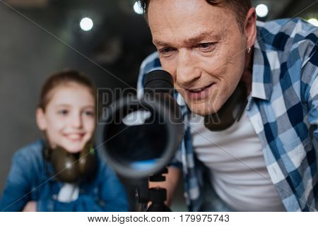 Optical telescope. Delighted positive pleasant man smiling and looking into the telescope while enjoying the activity