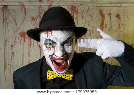 Evil clown doing a suicide symbol. Danger, desperation and fun concept