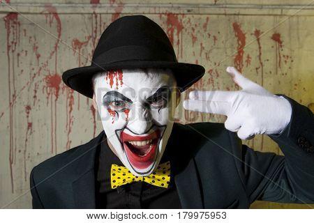 Evil clown doing a suicide symbol. Danger, desperation and fun concept