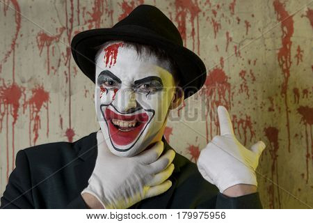 Evil clown hands by the throat on a wall background, suffocation, choking
