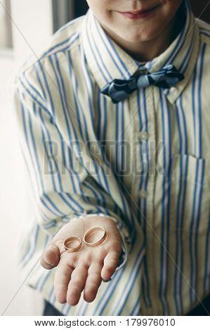 Young Cute Boy Holding Couple Of Golden Wedding Rings In His Hand, Ring Bearer With Two Platinum Eng