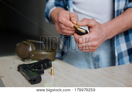 Preparing the weapon. Nice pleasant brutal man holding a bullet and putting into the cartridge clip while preparing his handgun for shooting